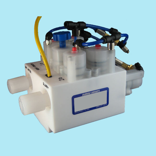 """PTFE block to which are attached valves and fittings. A blue-outlined label reads """"Malema Sensors - Boca Raton, FL, USA (800) 637-6418""""."""